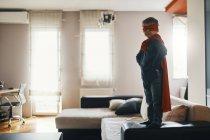 Pequeño niño vestido como un superhéroe de pie en la mesa de café en casa - foto de stock
