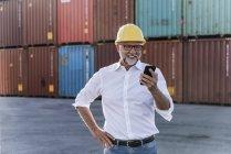 Homme d'affaires au port de fret, portant un casque de sécurité, utilisant un smartphone — Photo de stock