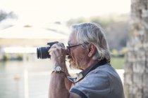 Старший фотографирует со своей камерой — стоковое фото