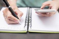 Mujer escribiendo notas en el diario, sosteniendo teléfono inteligente - foto de stock