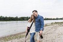 Glückliches Paar mit Bierflasche und Gitarre am Flussufer — Stockfoto