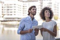 Empresário e mulher tendo uma reunião ao ar livre, usando tablet digital — Fotografia de Stock