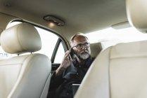 Reifer Geschäftsmann sitzt auf Rücksitz im Auto und telefoniert — Stockfoto
