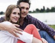 Ласкавий щаслива пара сидячи на березі річки — стокове фото
