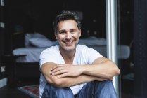 Портрет улыбающегося мужчины в пижаме дома, сидящего у французского окна — стоковое фото