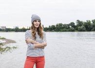 Портрет женщины в мохнатой шляпе, стоящей у реки — стоковое фото