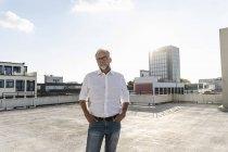 Пожилой человек, стоящий на крыше высотного здания, с руками в карманах — стоковое фото