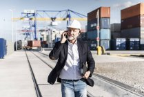 Businessman at cargo harbour, wearing safety helmet, using smartphone — Stock Photo