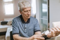 Senior man taking his blood pressure — Stock Photo