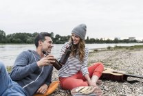 Happy couple relaxing at the riverside clinking beer bottles — Foto stock
