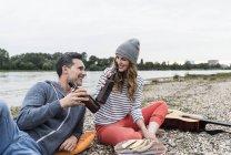 Glückliches Paar entspannt am Flussufer klirrende Bierflaschen — Stockfoto