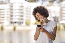 Giovane donna prendersi una pausa all'aperto, tenendo in mano una tazza di caffè e smartphone — Foto stock