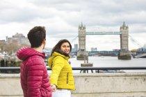 Uk, Londres, joven pareja caminando mano a mano en el puente sobre el Támesis - foto de stock