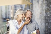 Coppia anziana in pausa in città, mangiare patatine fritte — Foto stock