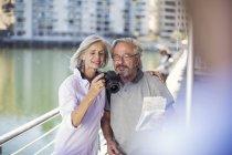 Старшая пара отдыхает в городе, фотографирует — стоковое фото