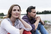 Couple sitting at the riverside thinking — Stock Photo