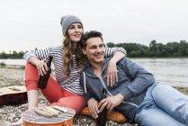 Счастливая пара с бутылками пива отдыхает на берегу реки — стоковое фото