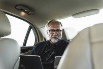 Geschäftsmann sitzt mit digitalem Tablet auf Rücksitz im Auto — Stockfoto