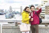 Великобритания, Лондон, молодая пара с кофе, стоящая на мосту через Темзу и делающая селфи со смартфоном — стоковое фото