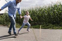 Mature man and little girl running on street, laughing — Stock Photo