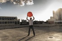 Mature man playing with orange fitness ball on rooftop of a high-rise building — Stock Photo