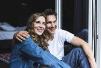 Glückliches Paar in Nachtwäsche zu Hause am französischen Fenster sitzend — Stockfoto