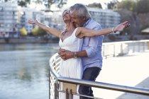 Старшая пара отдыхает в городе, обнимается за перила — стоковое фото