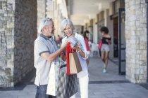 Casal sênior fazendo uma pausa na cidade, fazendo compras — Fotografia de Stock