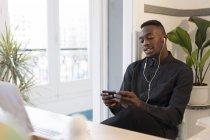 Портрет молодого бизнесмена, использующего смартфон и наушники в офисе — стоковое фото