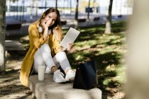 Lächelnde Frau sitzt mit Tablet auf Bank im Park und blickt in Kamera — Stockfoto