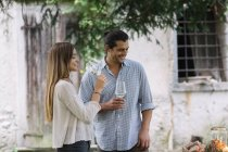 Coppia con bicchieri di vino avendo un pasto romantico candelight accanto a un cottage — Foto stock