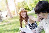Портрет смеющейся молодой женщины, развлекающейся в парке со своим сокурсником — стоковое фото
