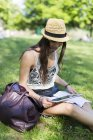 Young student sitting on a meadow in a park and using digital tablet — Stock Photo