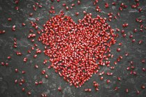 Corazón en forma de semillas de granada en pizarra - foto de stock