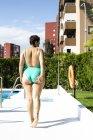 Задня думка про пухку молоду жінку, що йдуть поруч з басейном — стокове фото