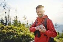 Sorrindo homem verificando seu telefone celular durante a viagem de caminhada — Fotografia de Stock