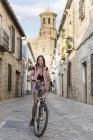 Espagne, Baeza, portrait d'une jeune femme souriante faisant du vélo en ville — Photo de stock