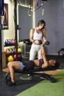 Personal trainer assistere il cliente con allenamento con i pesi, sollevamento manubri, sdraiato su panchina — Foto stock