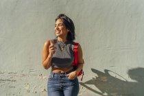 Портрет счастливой молодой женщины с рожком мороженого у стены — стоковое фото