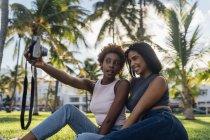 Две счастливые подруги делают мгновенное фото в парке — стоковое фото