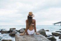 Rückansicht einer jungen Frau, die auf einem Felsen am Meer sitzt — Stockfoto