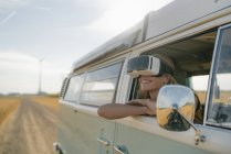 Smiling woman wearing VR glasses leaning out of window of a camper van — Stock Photo