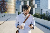 Mature man with takeaway coffee and headphones using cell phone in the city — Stock Photo