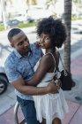 США, Флорида, Майамі-Біч, посміхаючись Ласкавий молода пара обіймаючи в місті — стокове фото