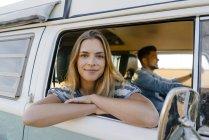 Porträt einer lächelnden Frau, die sich aus dem Fenster eines Wohnmobils lehnt, mit einem Mann am Steuer — Stockfoto