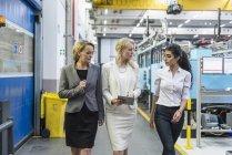 Три женщины с планшетом ходят и разговаривают в цехе завода — стоковое фото