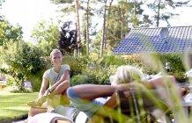 Женщина разговаривает со своим партнером в саду — стоковое фото