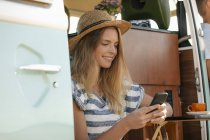 Smiling young woman using cell phone inside camper van — Stock Photo