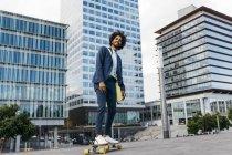 Spagna, Barcellona, giovane uomo d'affari che guida lo skateboard in città — Foto stock