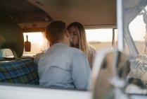 Pareja joven besándose en caravana al atardecer - foto de stock